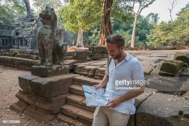 Jeune homme voyageant au Cambodge visiter les temples d'Angkor wat complexe et parcours de lecture de la carte