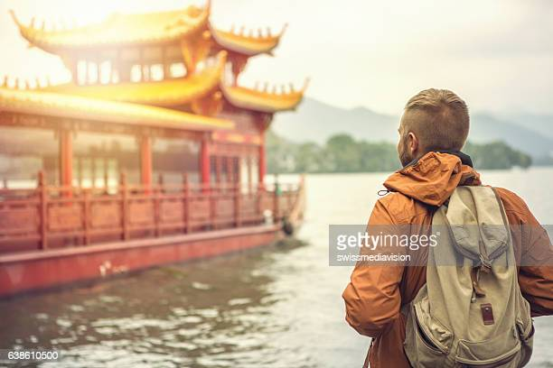 Young man traveling in China looks at pagoda on lake