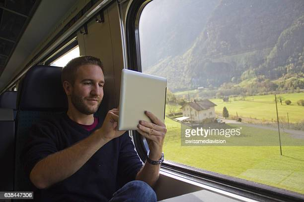 young man traveling in switzerland by train - swiss culture stock pictures, royalty-free photos & images