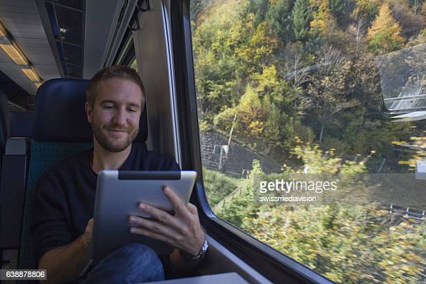 Young man traveling in Switzerland by train