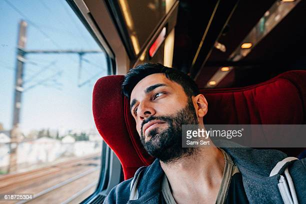 young man traveling in train - lost in thought - left eye stock photos and pictures