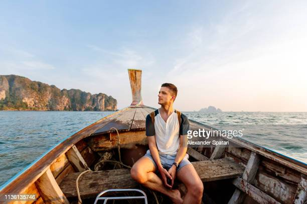young man traveling on a long-tail boat near islands in krabi, thailand - travel and not business stock photos and pictures