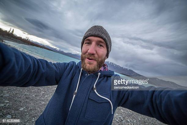 Young man traveling takes selfie with lake and mountain landscape