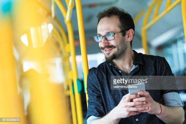 Young man traveling with bus and using smart phone
