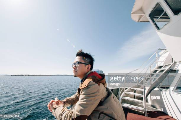 young man traveller enjoying the sea and breeze from cruise ship - passagier wasserfahrzeug stock-fotos und bilder