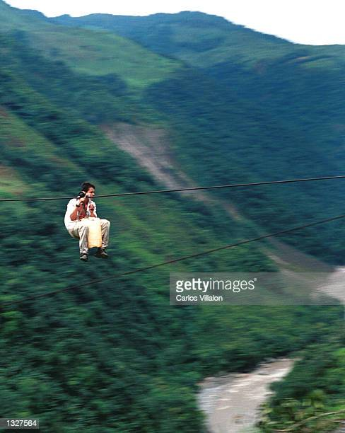 A young man travels home travels home by riding the iron cable April 1 2001 suspended 500m above the Black River in Guayabetal Colombia When children...