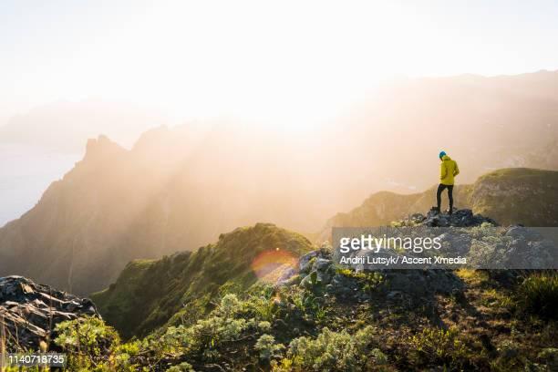 young man treks through alpine landscape, sunrise - montanha imagens e fotografias de stock