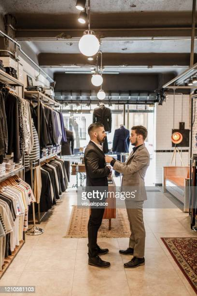 young man trying on a new suit - custom tailored suit stock pictures, royalty-free photos & images