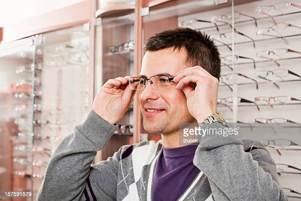 young man trying on glasses at opticians - izusek stock pictures, royalty-free photos & images