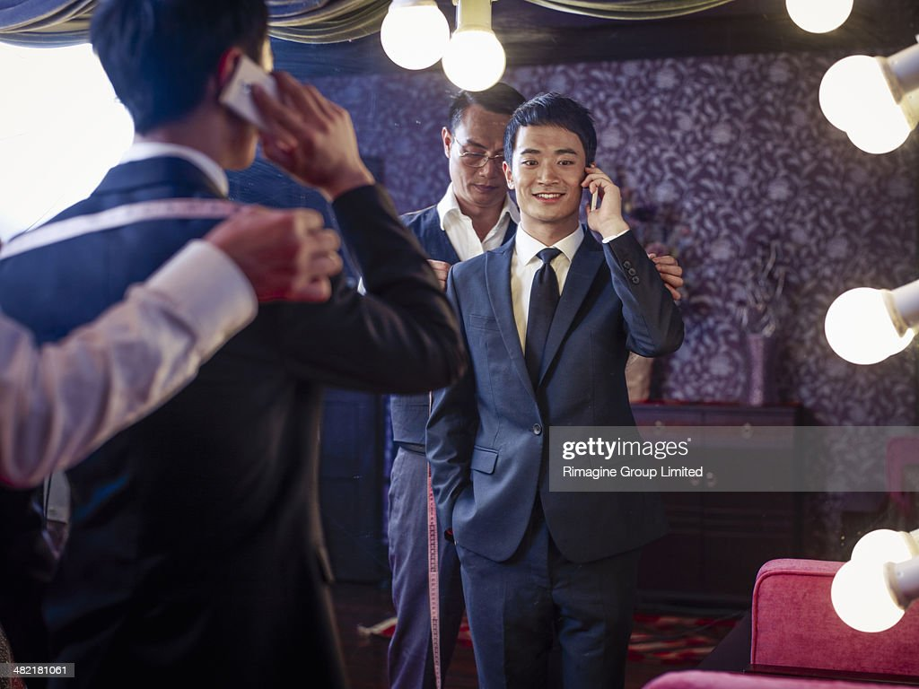 Young man trying on suit in traditional tailors shop : Stock Photo