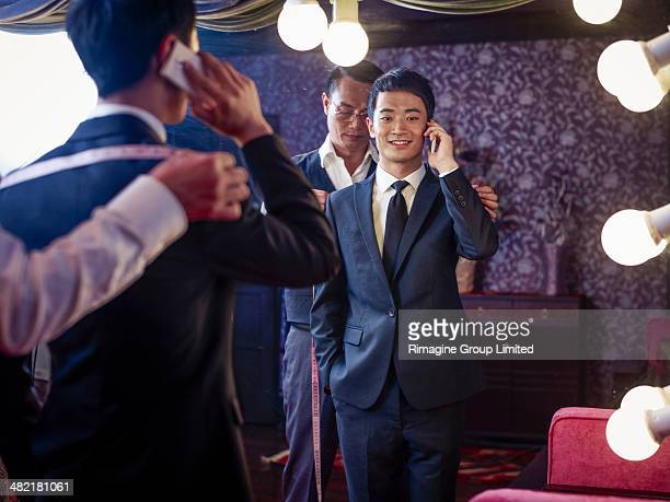 Young man trying on suit in traditional tailors shop