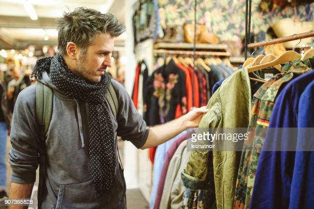 young man trying out clothes in london second hand market - ver a hora imagens e fotografias de stock