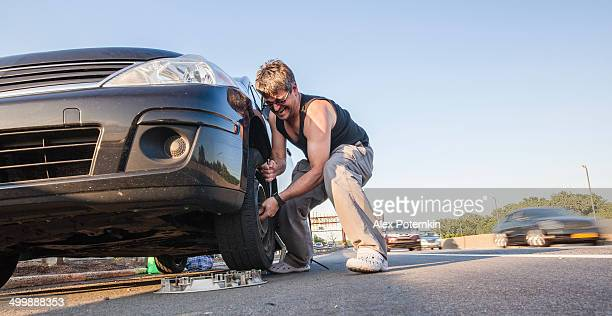 Young man trying to change the flattened tyre on the highway