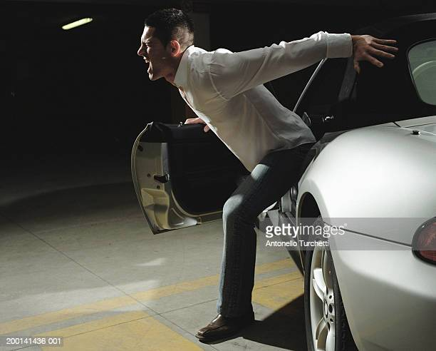 Young man trying to escape his car, profile