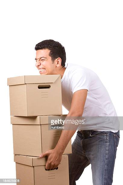 Young man trying to lift stacked heavy boxes