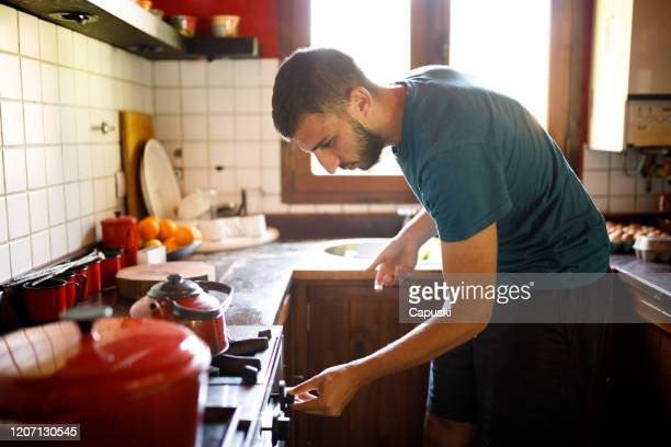 young man turning on the stove at kitchen - turning on or off stock pictures, royalty-free photos & images