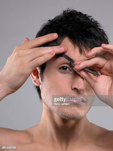 Young Man Tweezing Eyebrows