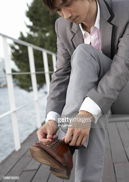 Young man tying his shoelaces