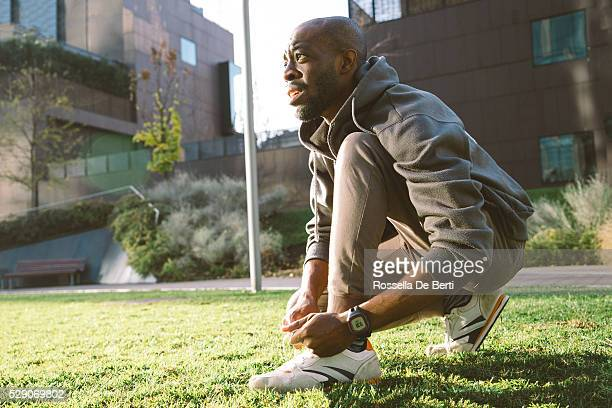 Young Man Tying His Shoelaces wearing sport clothes and smartwatch
