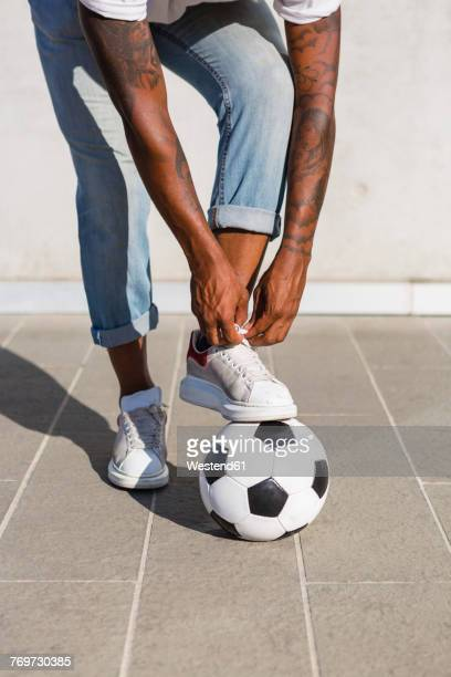 Young man tying his shoes on a soccer ball, partial view