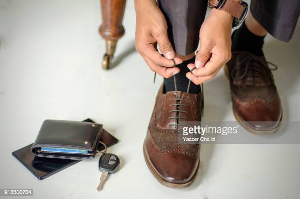 young man tying shoe laces - tying shoelace stock pictures, royalty-free photos & images