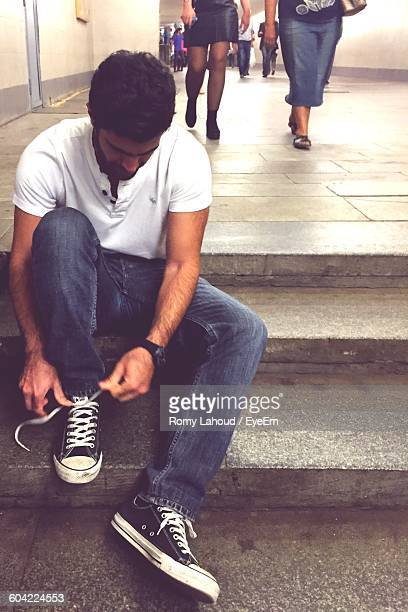 young man tying shoelace while sitting on steps - tying shoelace stock pictures, royalty-free photos & images