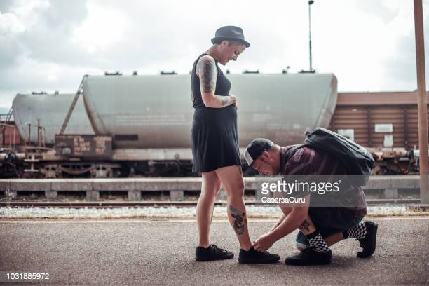 young man tying shoelaces for his pregnant girlfriend - doing a favor stock pictures, royalty-free photos & images