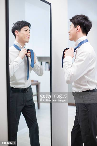 Young man tying tie in front of mirror