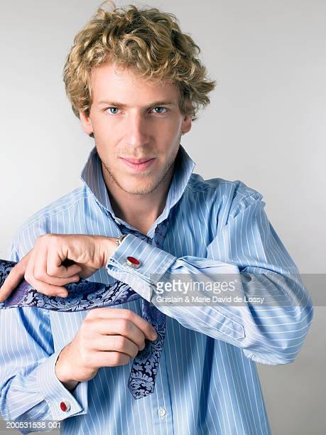 Young man tying tie, portrait