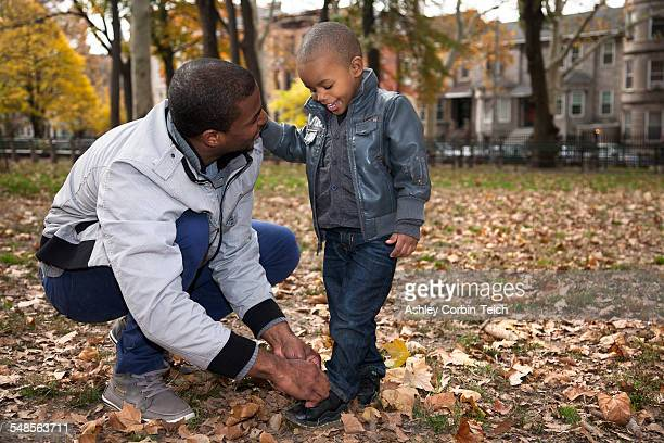Young man tying toddler sons shoelace in park