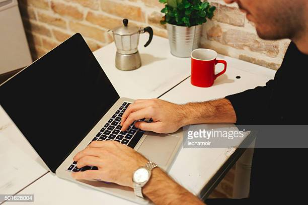 Young man typing at the laptop