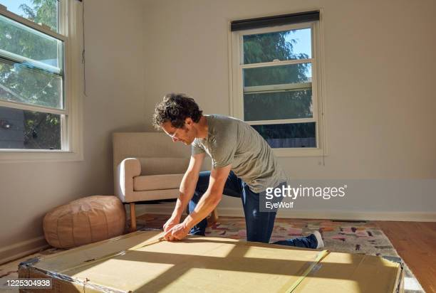 a young man unboxing a crib, preparing a nursery for his new family member - prenatale zorg stockfoto's en -beelden