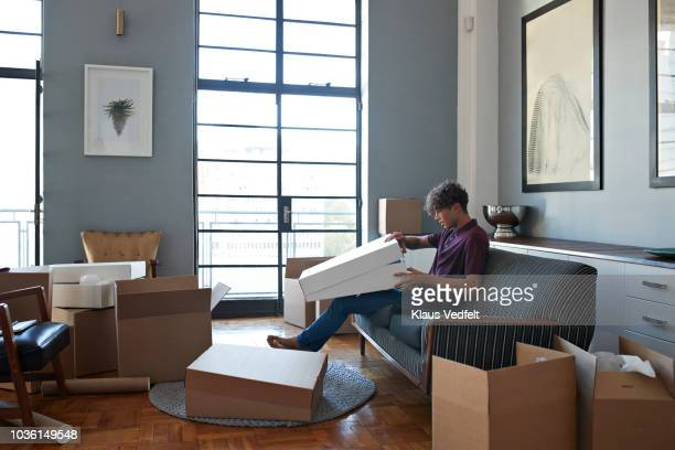 young man unwrapping package in apartment full of boxes - unpacking stock pictures, royalty-free photos & images