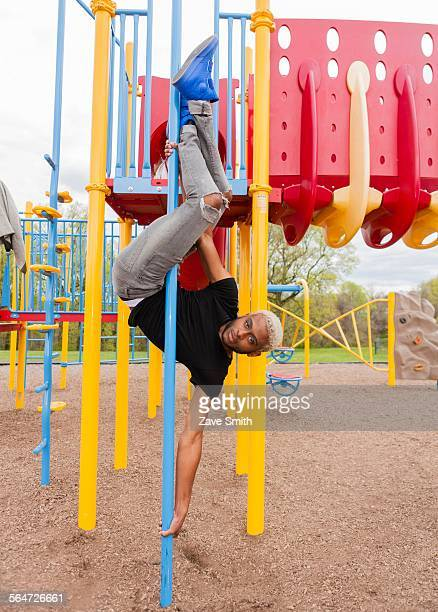 Young man upside down on pole in playground