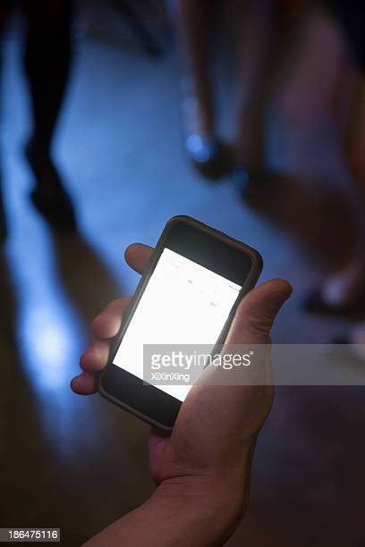 A young man uses a mobile phone in nightclub
