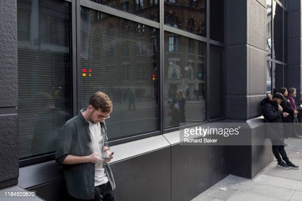 A young man uses his phone while vaping outside offices on a Farringdon Road on 20th November 2019 in the City of London England