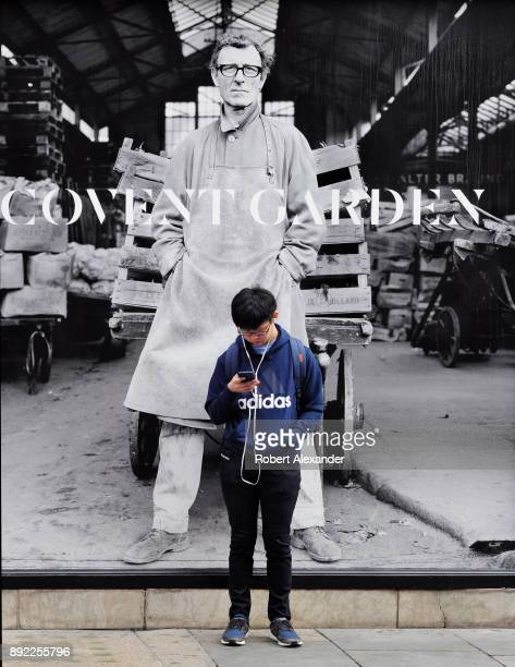 A young man uses his smartphone while standing in front of a large mural photograph in Covent Garden Market in London England