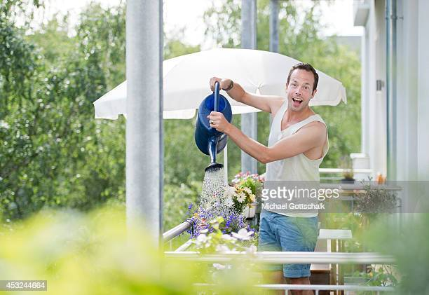 A young man uses his watering can to pour his flowers on the balcony on July 03 2014 in Berlin Germany