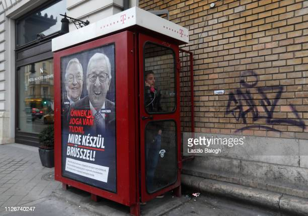 A young man uses the public phone next to billboard with portraits of European Commission chief JeanClaude Juncker and Hungarianborn US billioner...