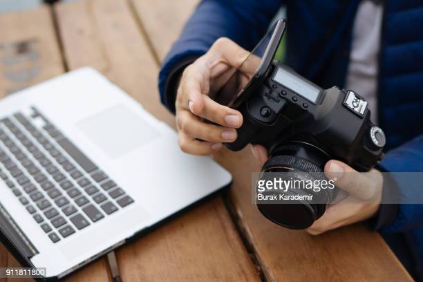 young man uses wireless connection between photo camera and smart phone - イメージ転送 ストックフォトと画像