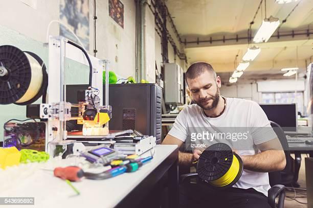 Jeune homme en utilisant une imprimante 3D dans un atelier de construction