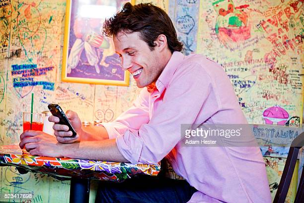 A young man using a cell phone inside a cafe and smiling.