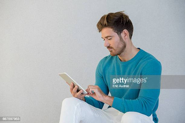 Young man using a digital tablet at home