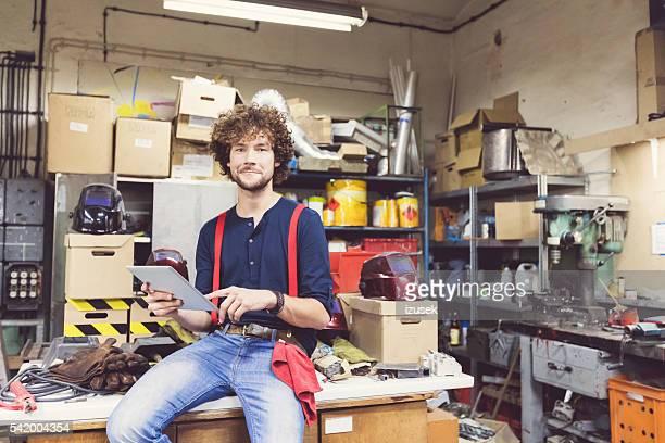 Junger Mann mit einem Digitaltablett im einer Konstruktion workshop