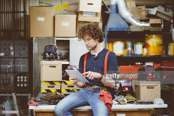 Junger Mann mit einem Digitaltablett in einem workshop