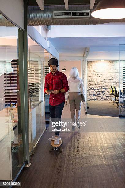 young man using a digital tablet on skateboard with colleague in office hallway - music halls stock pictures, royalty-free photos & images