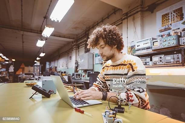 Junger Mann mit einem Laptop in einem elektronischen werkstatt