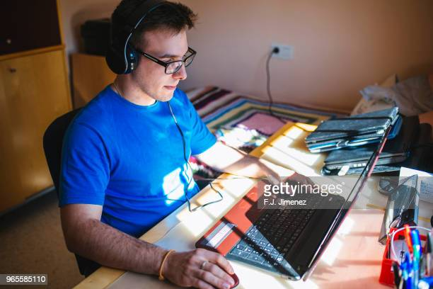 young man using a laptop in her room - gamer stock pictures, royalty-free photos & images