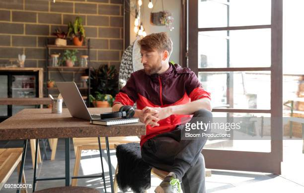 young man using a laptop - tracksuit bottoms stock pictures, royalty-free photos & images