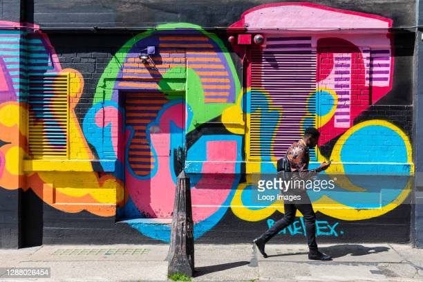 Young man using a mobile phone walks past colourful street art in Shoreditch.